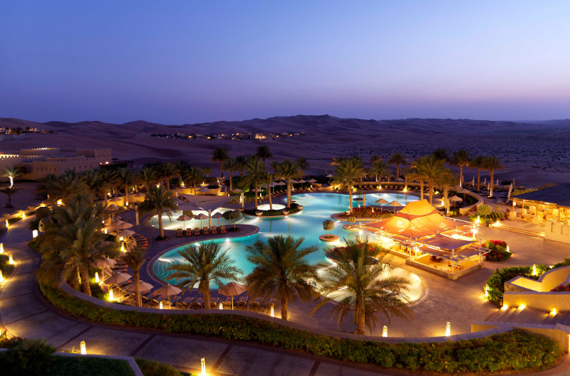 luxury hotel in desert pool at sunset