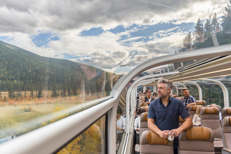 man on rocky mountaineer train looking out clear dome