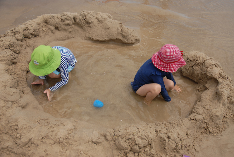 two children building a sea fort in iluka, new south wales