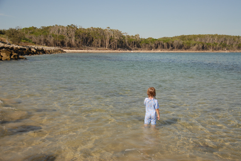 young girl at beach looking out to bushland in Iluka new south wales