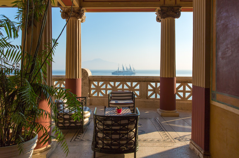 balcony overlooking gulf of naples with ship on horizon
