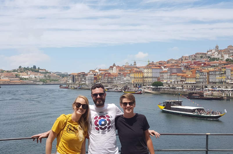 Three friends smiling at the camera with the colourful city of porto in the background