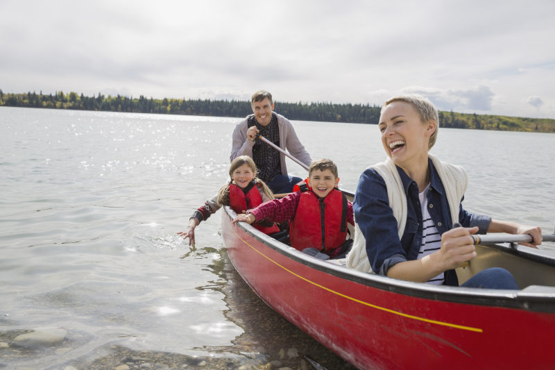 family in a canoe on a lake laughing