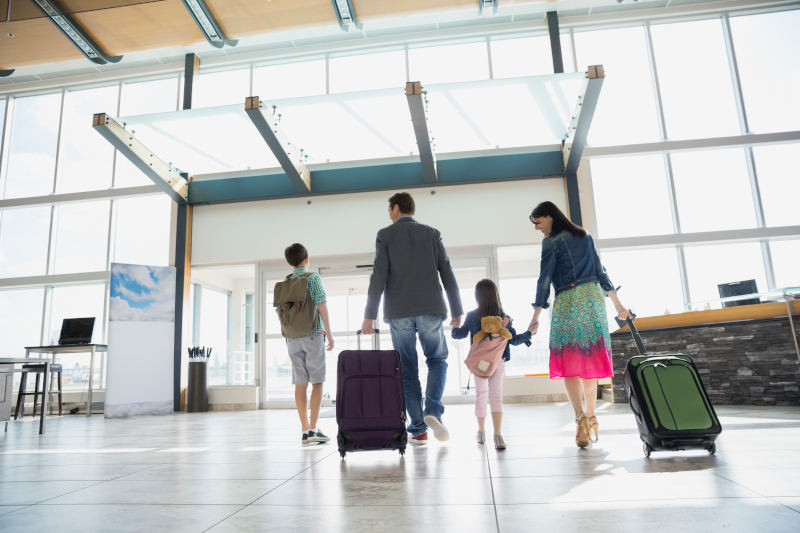 family walking towards departure gate at airport
