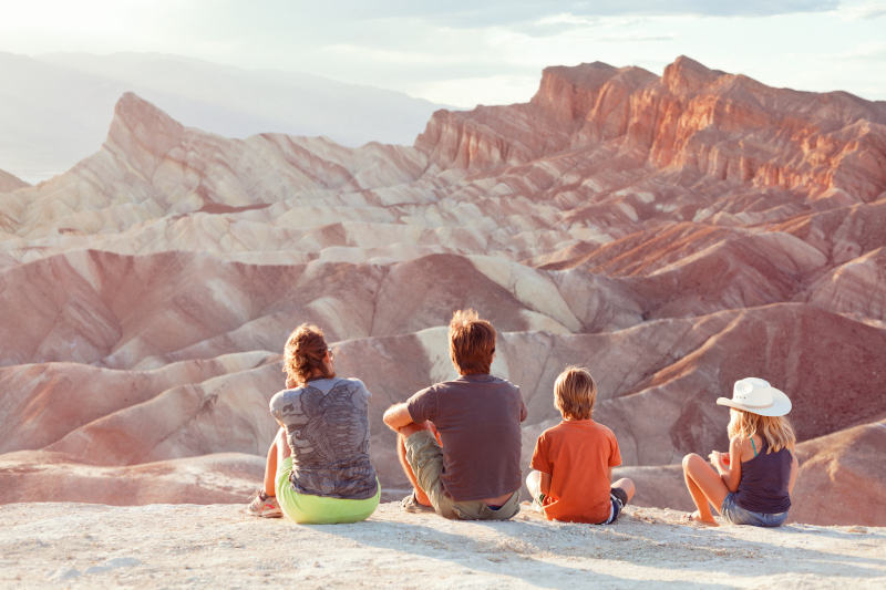 family sitting and taking in the view of a red canyon