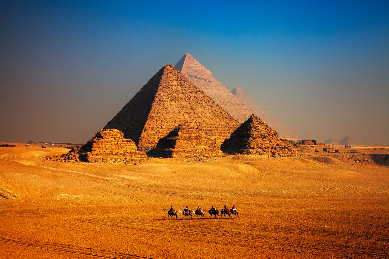 camel caravan in front of Egyptian pyramids