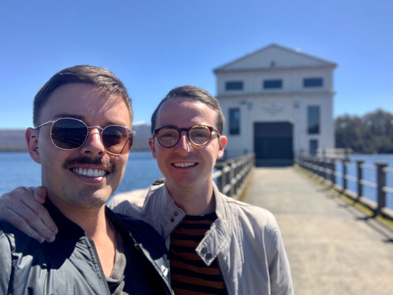 two men smiling and taking a selfie in front of the pumphouse