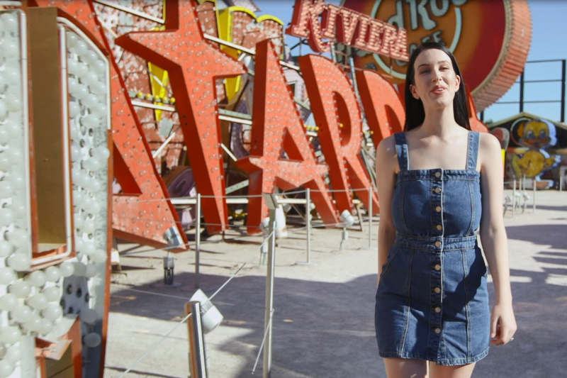 Laura walking through the Neon museum during the day with vintage Las Vegas signs in the background