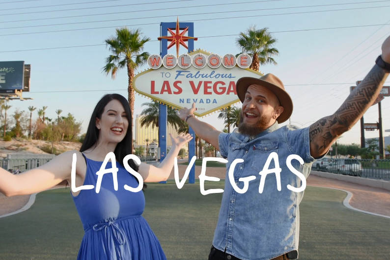 Laura and Troy standing excited in front of the Las Vegas sign