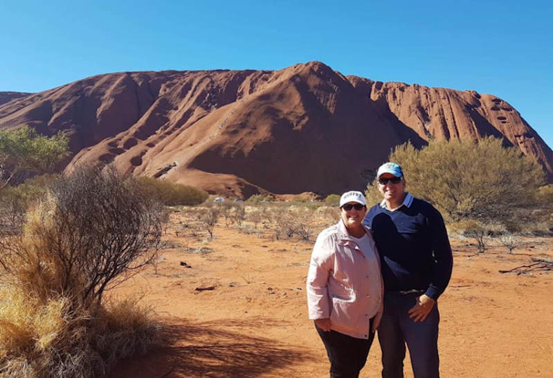 Karen and Cameron standing in front of Uluru for a photo