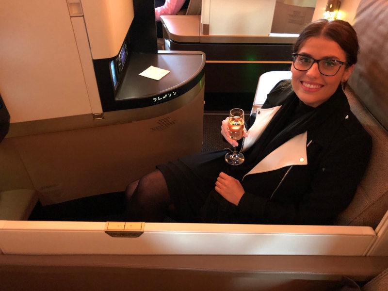 Woman sitting in a business class seat holding champagne and smiling