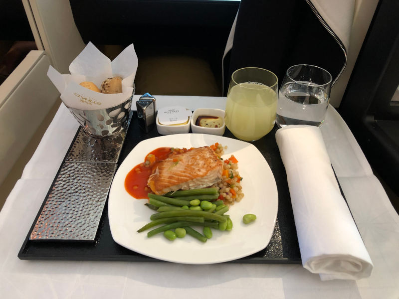 A photo of a meal in business class. Salmon with green beans, champagne and also bread.