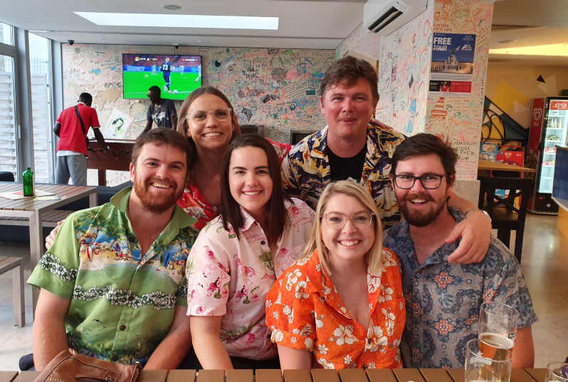 A group of six people looking at the camera and smiling. They are wearing matching hawaiian shirts