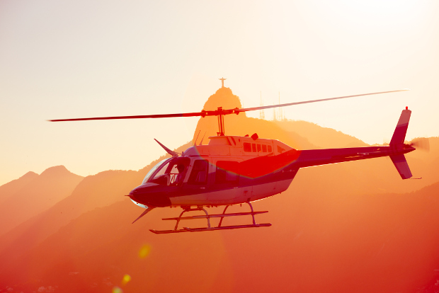 A helicopter flies around the Christ the Redeemer statue in Rio de Janeiro, Brazil, at sunset.