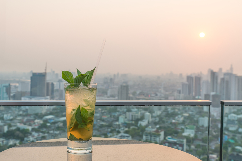 A close-up of a mojito on a rooftop bar.