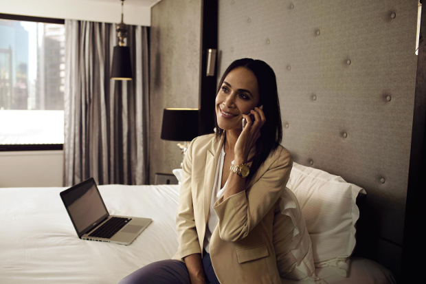 A woman calling someone from her hotel room