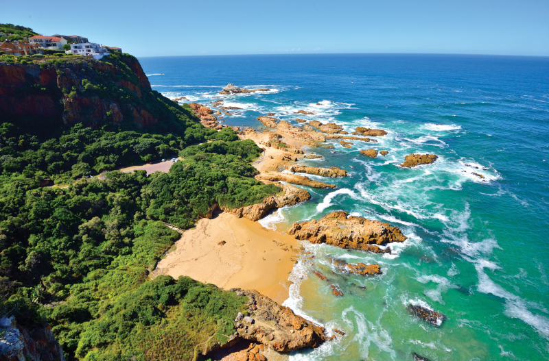 A sunny day at Knysna Heads, the ocean is meeting the sand and headland