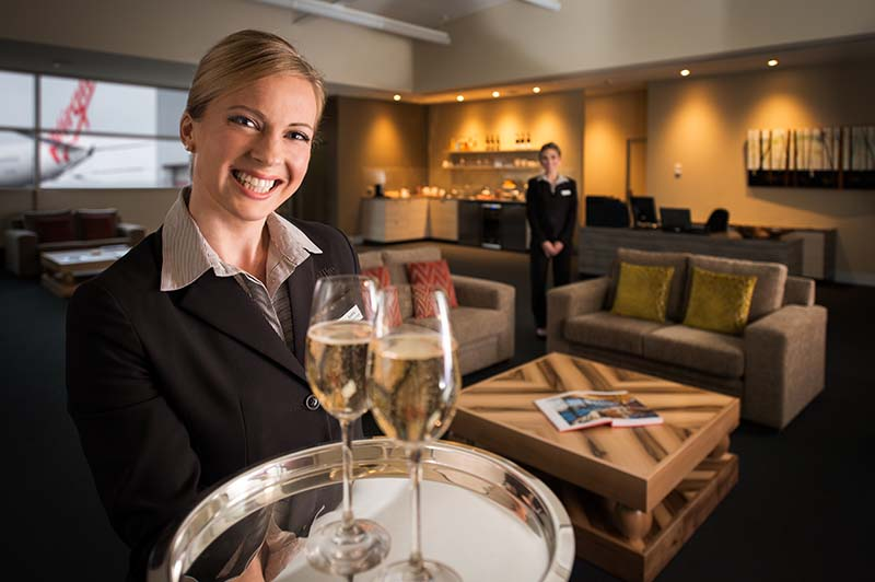 waiter serves champagne in saffire lounge at hobart airport
