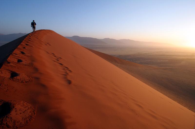 Man walking along a sand dune in Namibia