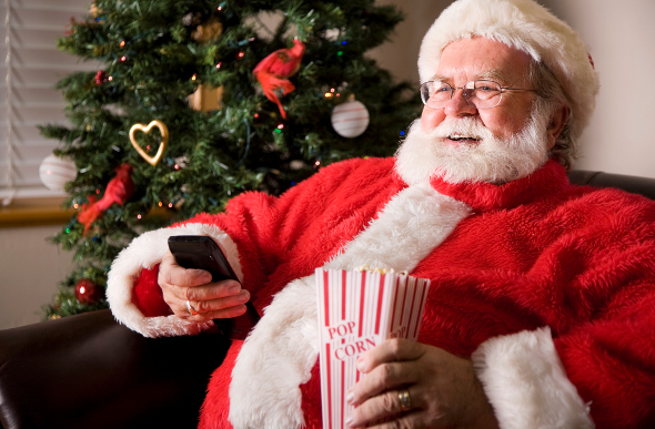 Santa watching a movie holding a remote and popcorn