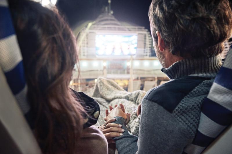 A couple enjoy a movie on the deck of a Princess cruise ship.