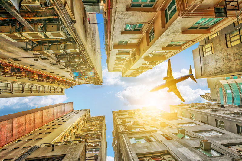 A plane passes over residential buildings in Hong Kong, as viewed from below.
