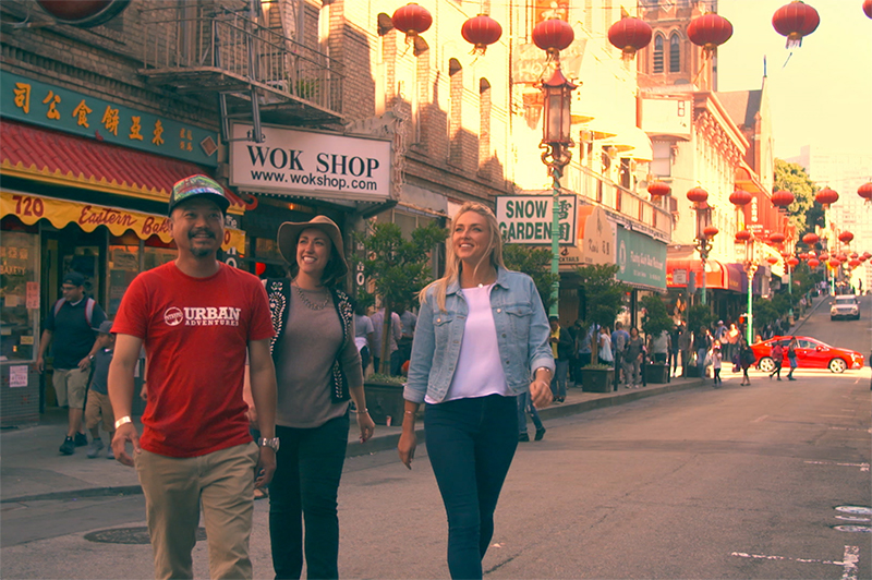A man and two women walk through San Francisco's Chinatown.