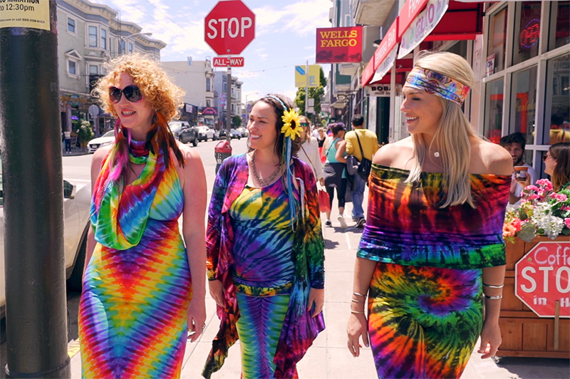 Three women in 1960s clothes walk along Haight in San Francisco.