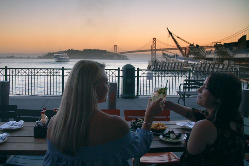 Two women dine at Hog Island Oyster Bar and watch the sun set over the water in San Francisco.