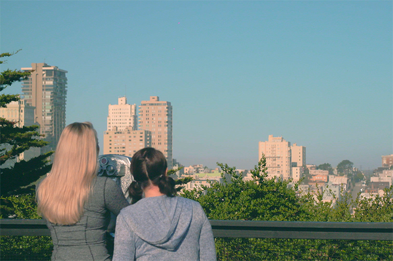 Two women look at the viewfinder view from Telegraph Hill in San Francisco.