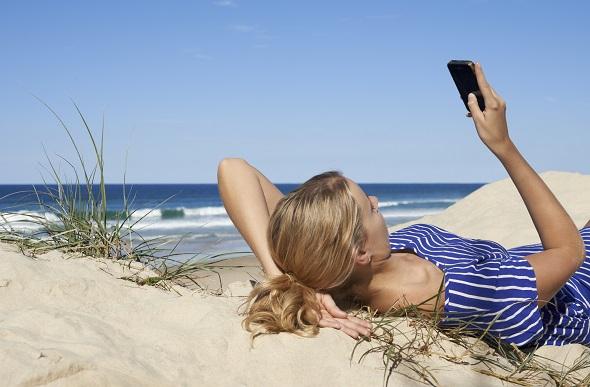 girl texting lying on beach