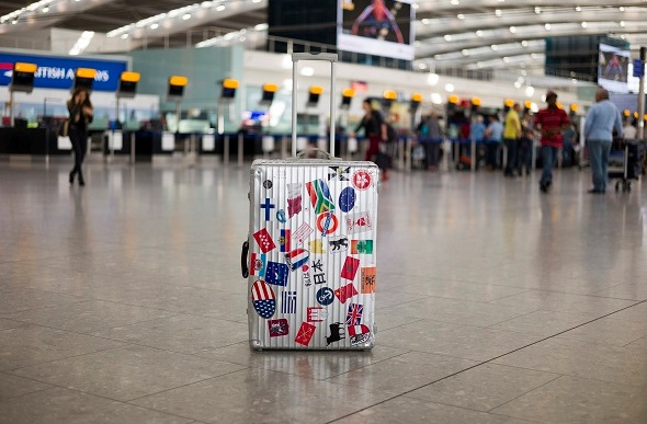 lone suitcase in airport with stickers on