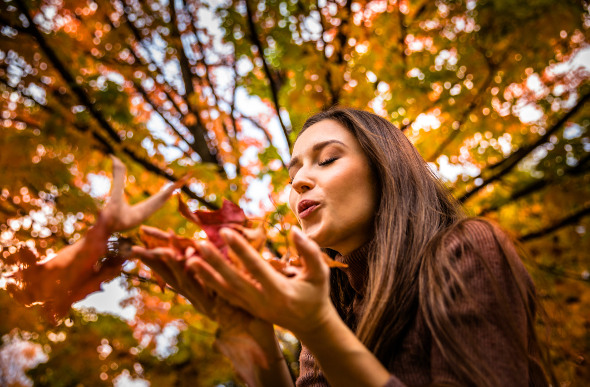A woman plays with Autumn leaves.