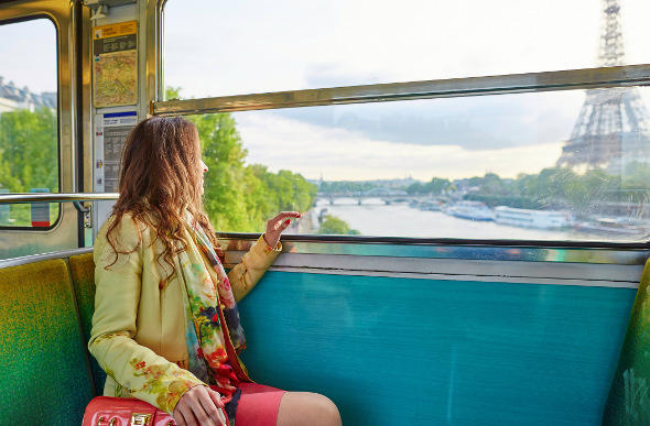 A woman stares at the Eiffel Tower through a train window.