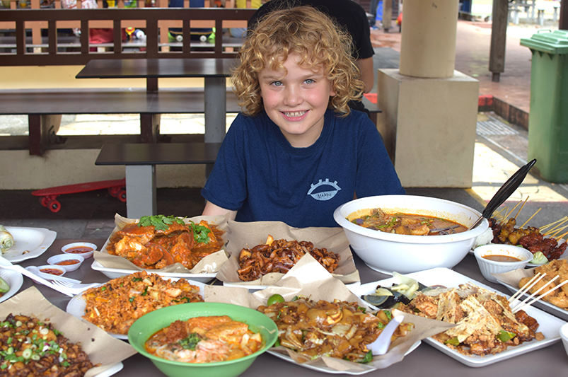 Boy with food from Singapore's hawker centres on table