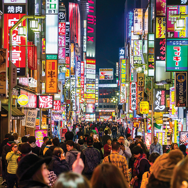 Crowds of commuters fill the streets of neon-lit Shinjuku in Tokyo at night