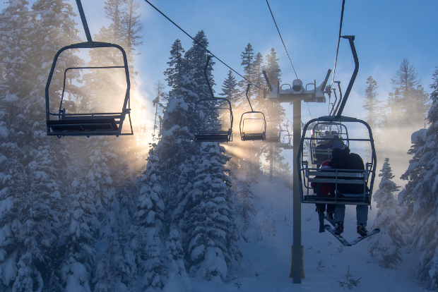 Skiiers on chairlift in sunlight