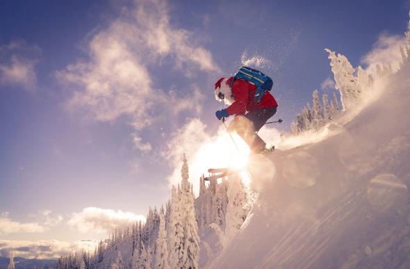 A man dressed as santa skiing down a slope