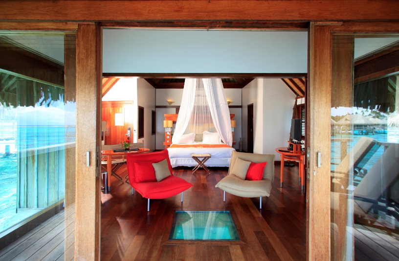 looking into an overwater villa and into the main bedroom. There is a small glass bottom built into the floor