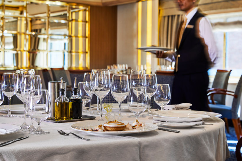 dining setting with waiter behind onboard silver cloud