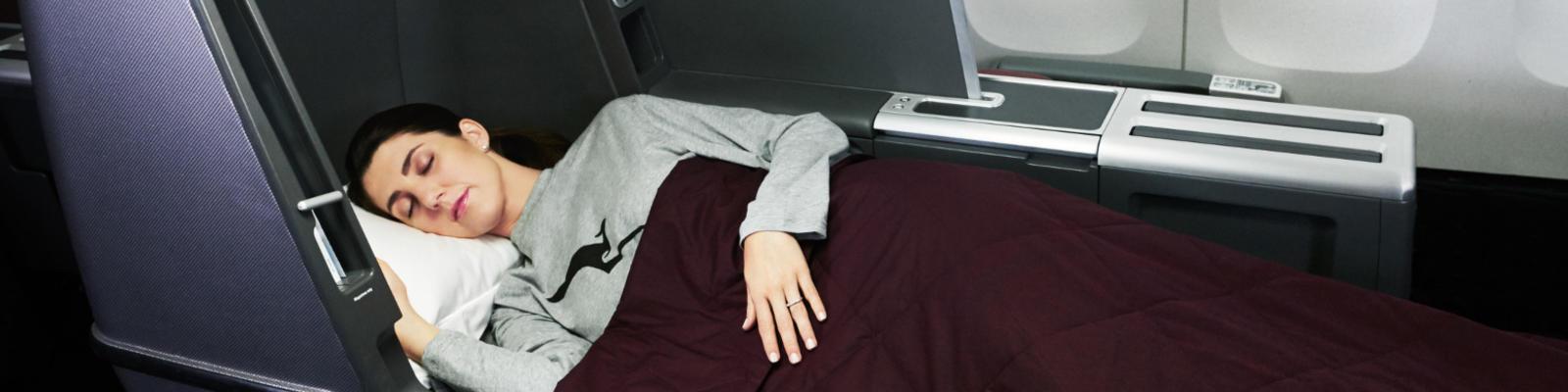 A woman sleeping on her Qantas Business Class lay flat seat