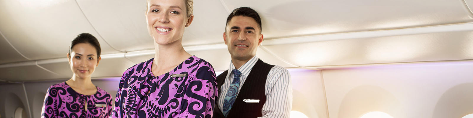 Three Air New Zealand flight attendants inside an aircraft.