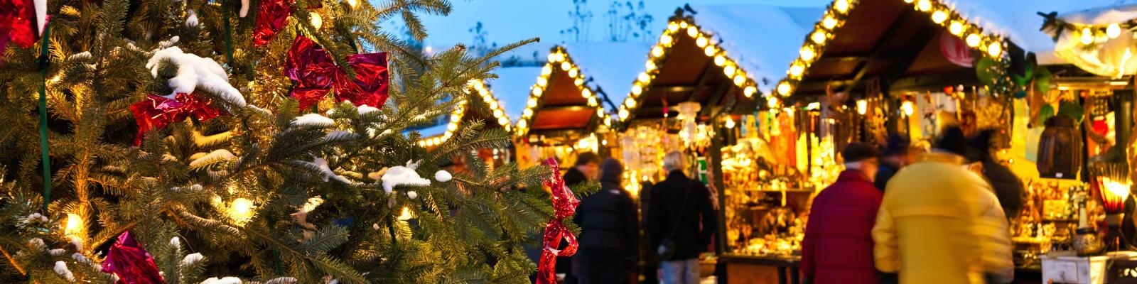 Christmas tree and people browsing the christmas market