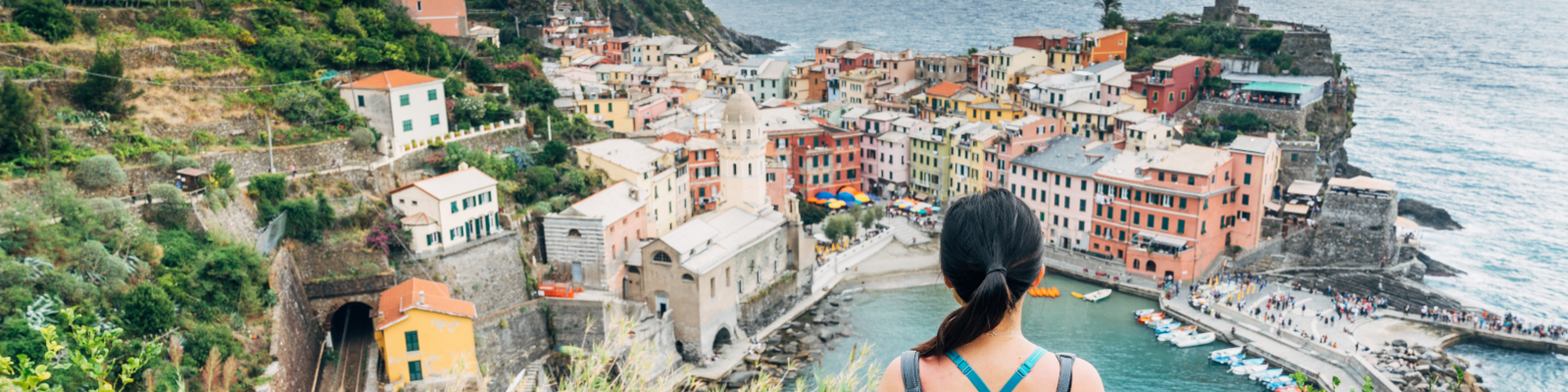 Girl looking out onto the sea and Cinque Terre in Italy. The buildings are colourful