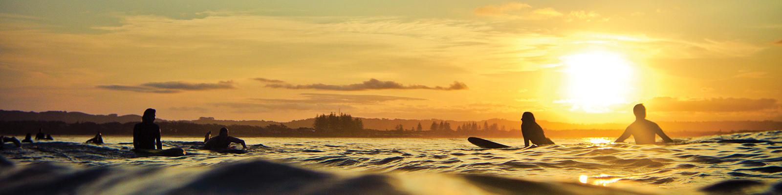 byron bay surfers at sunrise