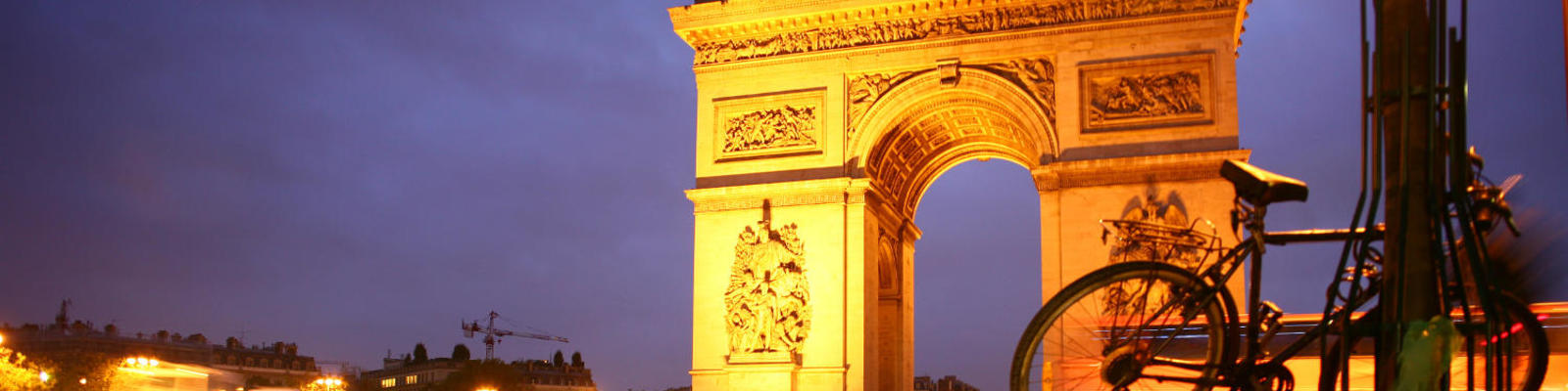 A bicycle leans against a lamp post in the glow from Paris's Arc de Triomphe, which is illuminated by night.