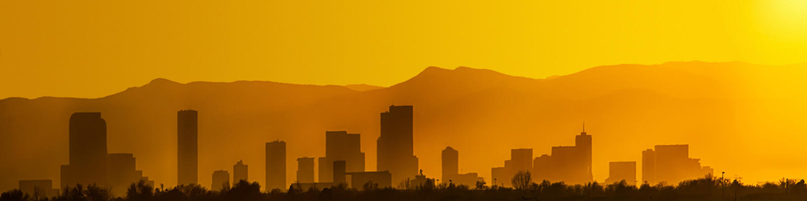 The Denver skyline silhouetted against a golden sunset.
