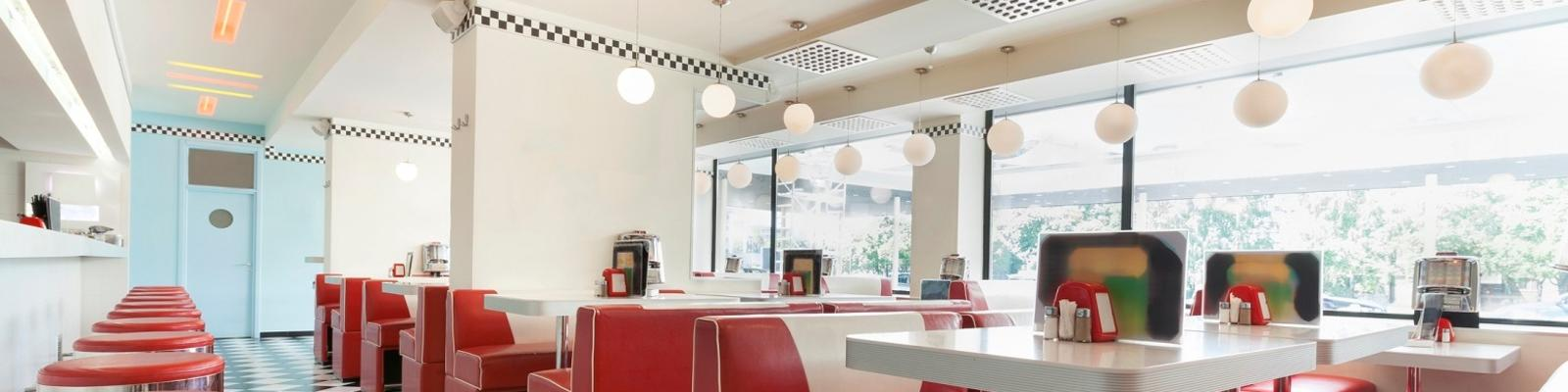 An American diner restaurant style in black and white tiles and red booths. Photo: Getty Images.