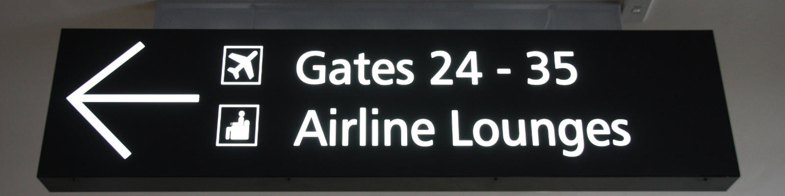 A sign in the airport pointing to gates and lounges