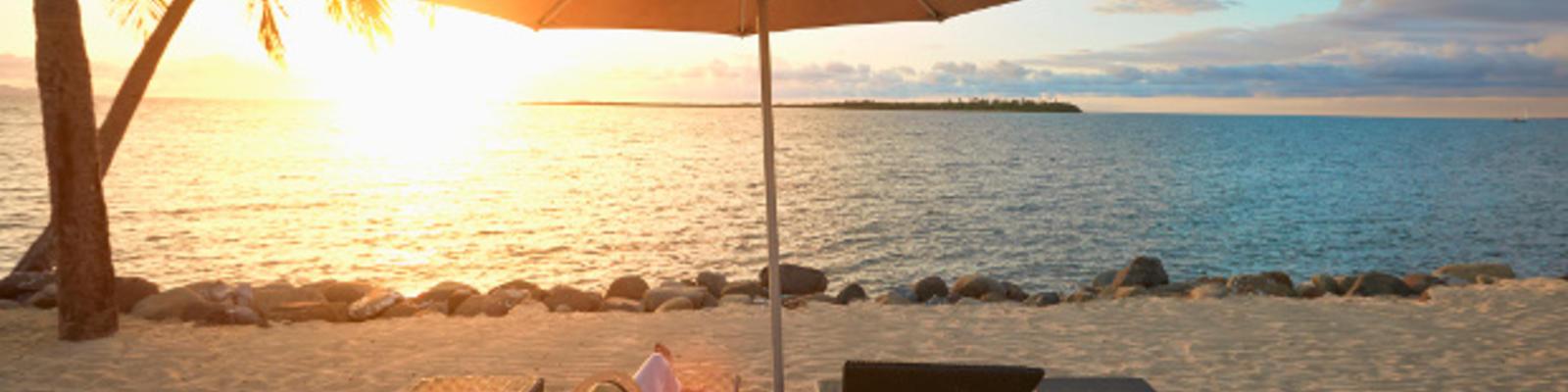Loungers on the Fijian beach at sunset